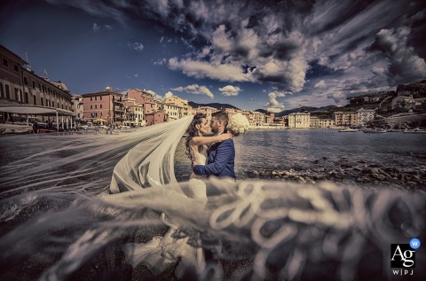 Sestri Levante Baia del silenzio wedding portrait with the groom and bride with her long veil over the water