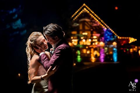Photo romantique de la mariée et le marié s'embrassant sous les lumières du lieu au château de montagne Della Terra (Estes Park, CO)