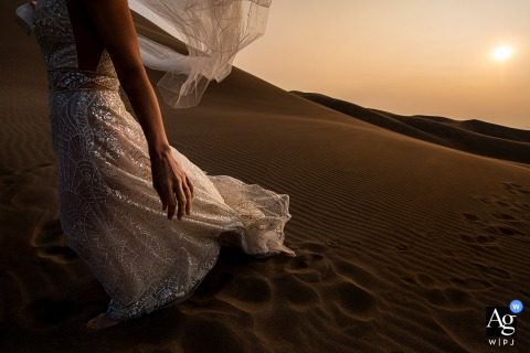 Detail photo of bride's dress and veil on sand dunes at the Great Sand Dunes National Park (Mosca, CO)