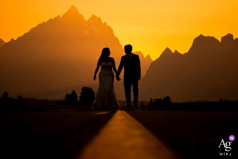 Grand Teton National Park wedding portrait of the bride and groom walking down street at sunset
