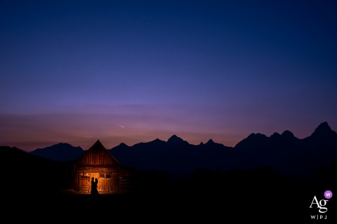 Silhouette photo of bride and groom against a barn at sunset at the Grand Teton National Park in Jackson, WY