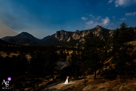 bride and groom portrait in front of vast mountain range at the Black Canyon Inn in Estes Park, Colorado