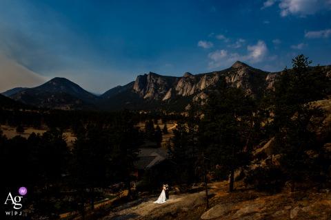 Braut- und Bräutigamporträt vor der weiten Bergkette am Black Canyon Inn im Estes Park, Colorado