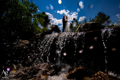 Braut und Bräutigam, die auf Wasserfall auf Spruce Mountain Ranch in Rittersporn, CO stehen