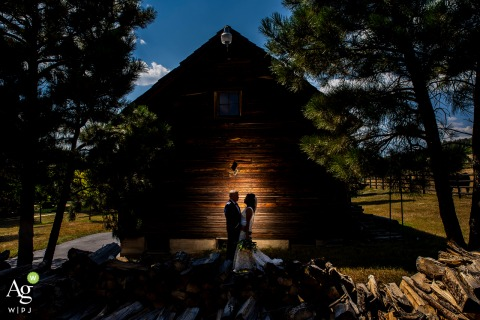 Spruce Mountain Ranch, Larkspur, CO creative wedding day portrait of the bride and groom standing by a lit rustic barn