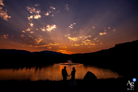 Bride and groom silhouette next to lake at sunset at Spruce Mountain Ranch in Larkspur, CO