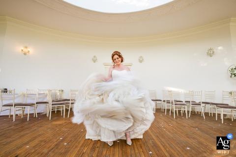 Die Braut hat Spaß mit ihrem Hochzeitskleid an der Rezeption in der Barton Hall, Kettering, Northants