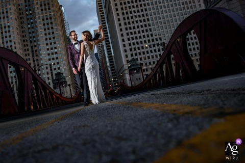 Newlywed couple portrait on a bridge by their reception at the River Roast in Chicago, IL