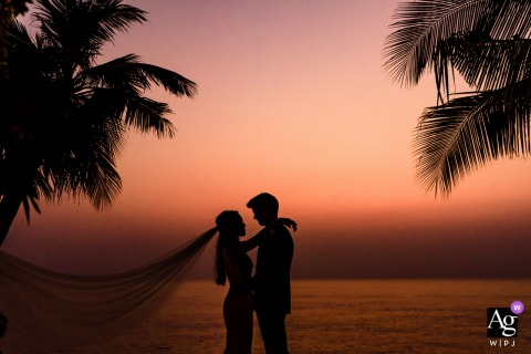 Sunset Vietnam wedding portrait of the bride and groom with palm trees and orange sky