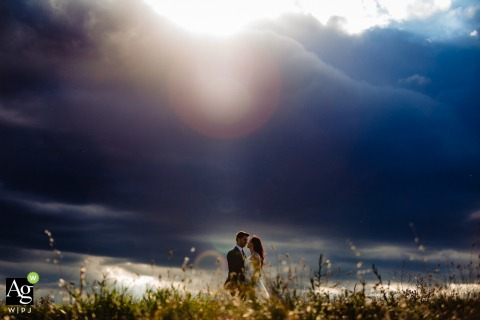 val d'Orcia - Italy fine art wedding portrait image showing the incredible sky covered with clouds and only a ray of light with illuminates the newlyweds