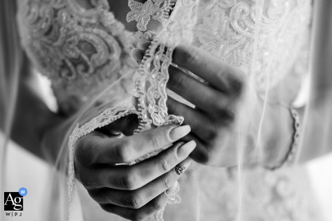 Italian wedding image of the hands of the bride while she is nervously holding her veil