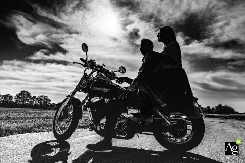 Hesse retrato de boda en blanco y negro de la pareja nupcial en motocicleta bajo un espectacular cielo con nubes