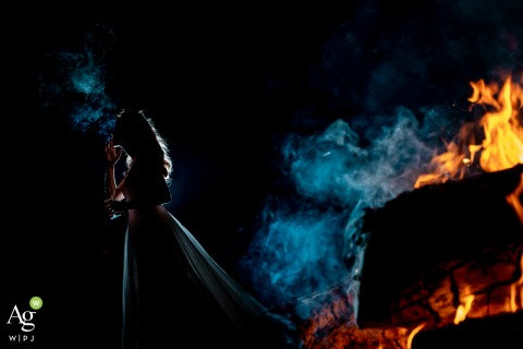 Artistic wedding photo from Les Hauts de Pardaillan, France of the Bride smoking by the fire place