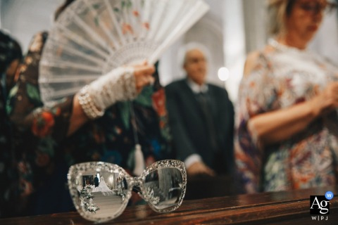 Chiesa Riflessi artistic wedding photo of reflective sunglasses and a guest with a fan in the church ceremony