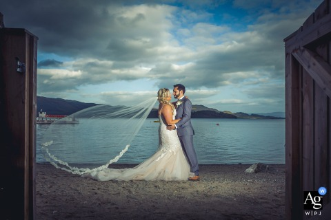 Bride and groom framed by gate on a beach in Scotland