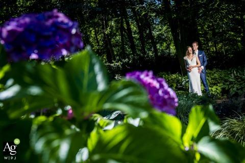 Retrato creativo del día de la boda de los Países Bajos con flores púrpuras para llenar el marco