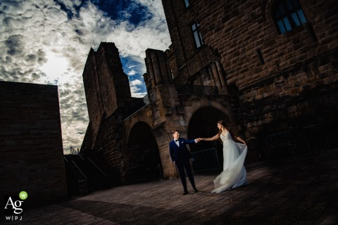 Hambacher Schloss artistic wedding couple portrait with some fun Dancing against the towering buildings
