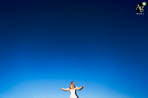 Ratež, Slovenia creative wedding day portrait of the Couple standing on the top of the hill with a clear, blue sky behind and over them