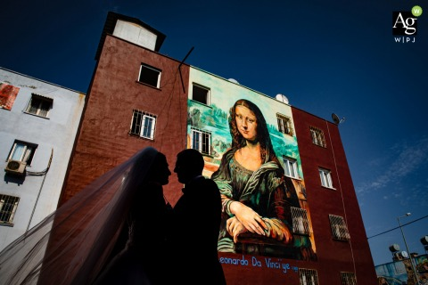 Mersin, Turkey fine art wedding portrait image of the couple in backlight posing in front of the Mona Lisa painting on a building