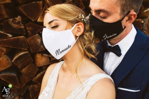 Slovenia creative wedding Couple having on masks for portrait photos with bride and groom signs on them by the stacked firewood