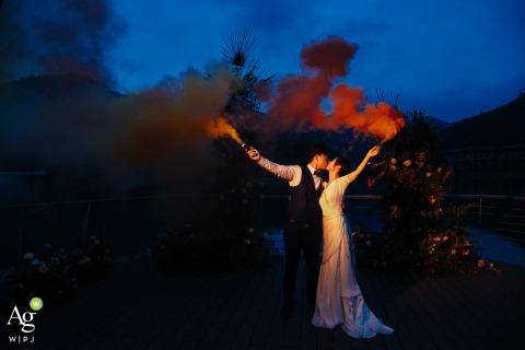 Künstlerisches Hochzeitspaarporträt des Fujian, China des Paares beleuchtet in der Dämmerung, die rote Rauchbombengranaten hält