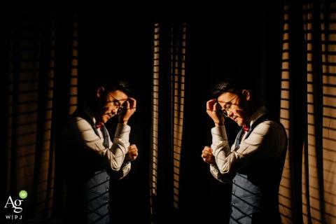 Kreatives Hochzeitstagporträt von Fujian, China des Bräutigams, der in gutem Licht mit einem Spiegel fertig wird