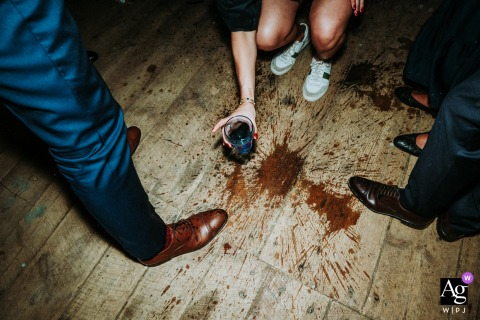 Artistic wedding photo from mill of the field of a glass falling on the Dancefloor