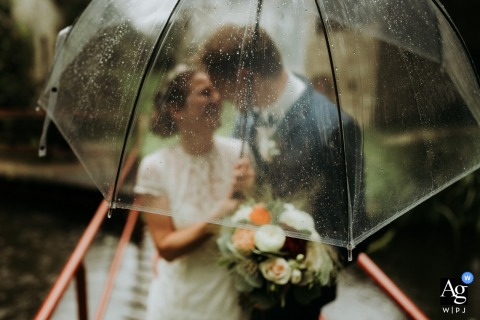 Image from mill of the field France	with the bride and groom under a transparent umbrella