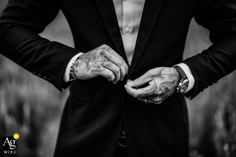 Vietnam artistic wedding photo of the man fastening his suit jacket buttons at the Ceremony Location