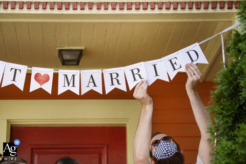 "Home wedding image from Cambridge, Massachusetts of the Officant/brother of bride hanging up ""Just Married"" sign after ceremony"