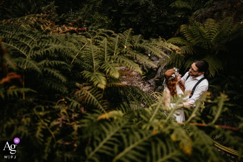 Münster, North Rhine Westphalia Bride and groom pose in ferns for green wedding day portraits