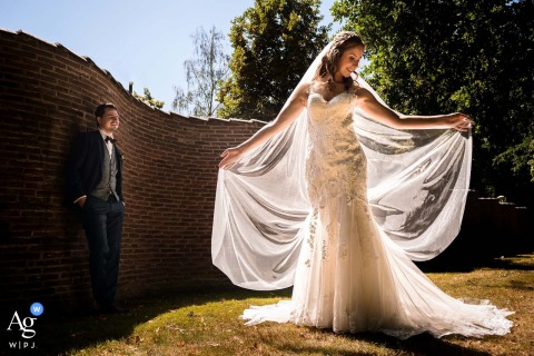 The bride is standing like an angel in the sun, showing her dress to the groom at the wall In Driebergen at the Sparrendaal Mansion