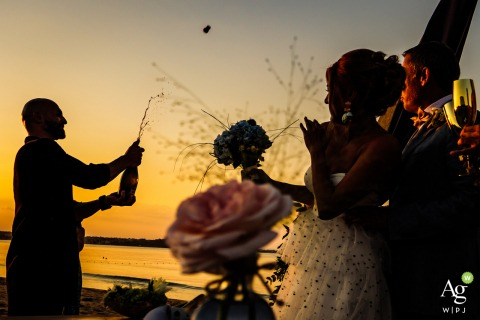 Bulgaria, Papur Beach fine art wedding detail photography picture showing The best man is opening Champagne in the sunset