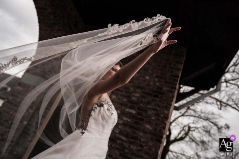 The bride is holding her dress in the harsh winter wind at Kasteel Daelenbroeck near Herkenbosch