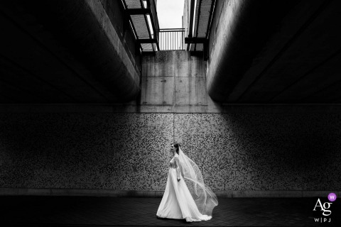 The bride is walking in the passage under the Leidsche Rijn bridge in Utrecht, perfectly in the light catching the wind