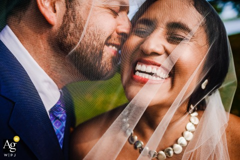 A couple laughs together under a veil while taking wedding portraits at Lincoln Park in Chicago, Illinois