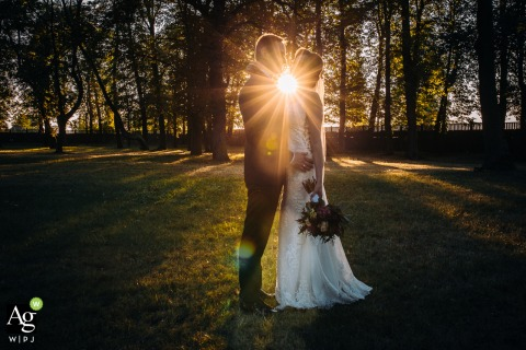 Gutow Castle, Kalisz, Poland fine art wedding portrait image of The young couple hugging in the park, wrapped in the rays of the setting sun
