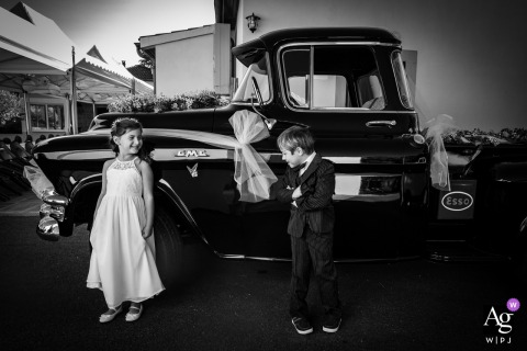 Children pose in front of the bride and groom's car at this Fleurance, France wedding