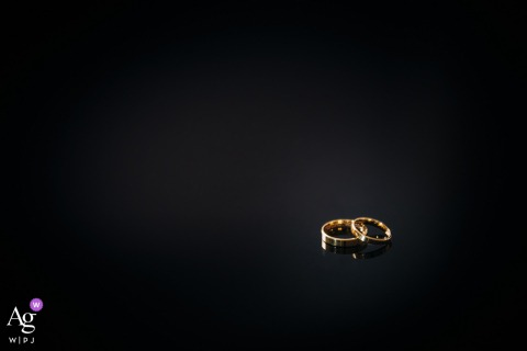"A close-up of the wedding rings of the bride and groom lying on a dark table at the ""On the hill"" Mansion in Lodz, Poland"