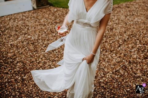 UK bride clasps onto her dress and drink on a wintry day at the wedding venue