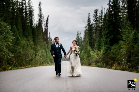Emerald Lake, Yoho National Park, BC, Canada bride and groom on the road and Running together