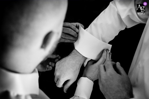 Philadelphia wedding detail of the groom getting a little help with his dress shirt from the guys