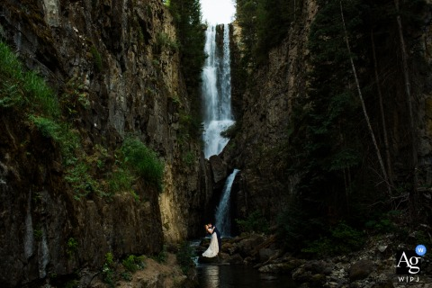 Wedding portrait of a couple kissing in front of waterfall during their Hike in Telluride, Colorado