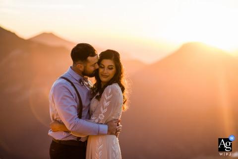 Het huwelijksportret van het Rocky Mountain National Park van de bruidegom die de bruid op de wang kust tijdens deze zonsondergangsessie