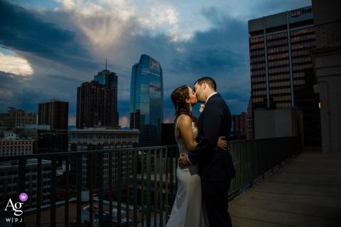 Colorado paar kussen bij zonsondergang op de top van het Magnolia Hotel in Denver