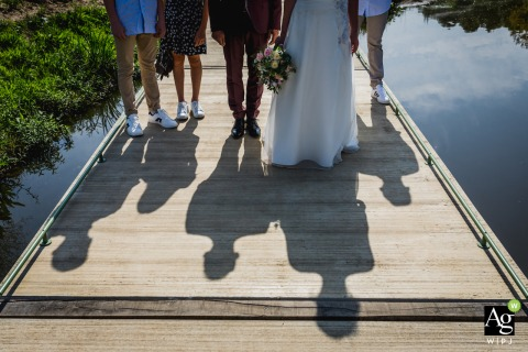 Flanders couple posing for a wedding picture of the family shadows on the wooden boat dock boardwalk