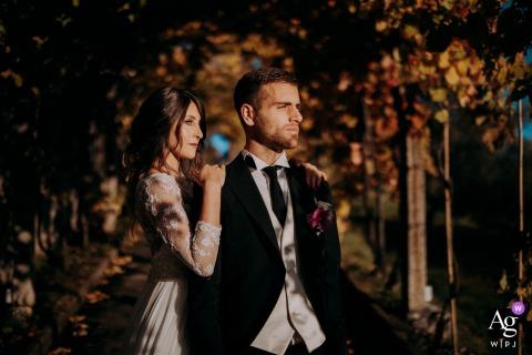 Villa Garavaglia, Cortona foto artística do casamento tirada enquanto a noiva abraça o noivo por trás, eles estão dentro de um túnel coberto de flores enquanto o sol se filtra pelos galhos