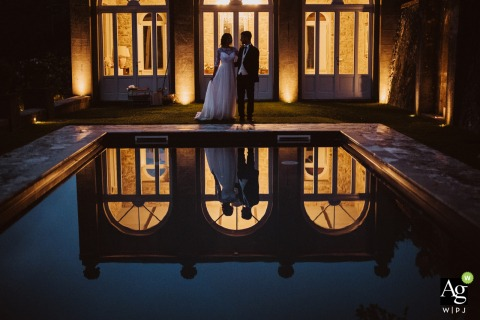 Villa Garavaglia, Cortona wedding couple posing for a portrait causing night reflections as the couple are reflected on the pool with the lights on the villa behind