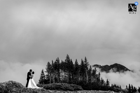 Arapahoe Basin, CO artistic wedding image showing The clouds creating a layer between mountains as the couple poses for a moment on top of Loveland Pass