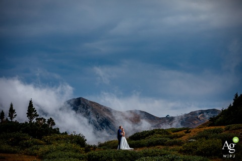 Arapahoe Basin, CO wedding couple posing for a portrait while Standing on top of Loveland Pass with the Ski Area in the background with a layer of low clouds in-between